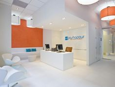 The entry is right off a busy street, so the clinic has a strong street presence.  White walls and white stone floors, along with blue and orange Venetian plaster accent walls, were inspired by Mediterranean architecture and scenery. Photo: Geoffrey Hodgdon