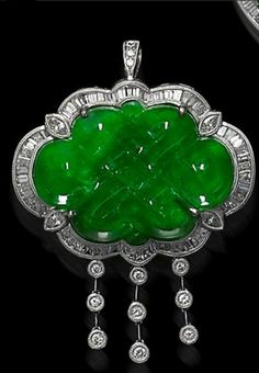 A jadeite and diamond brooch/pendant The brooch pendant set with a green jadeite, measuring approximately 29.4 x 21.5mm, carved as a knot symbolizing good luck, within a surround of baguette and marquise-cut diamonds, suspending a fringe of brilliant-cut diamonds. Mounted in 18 karat white gold.