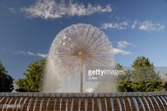 'A spherically shaped fountain sprays water against a blue sky with some clouds present and trees in the background. Water channels are spilling over in the forground. Horizontal color Photograph...