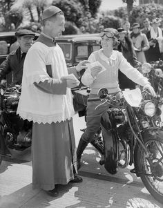 A reverend blesses the motorcycle of a woman who is learning to drive, 1938.