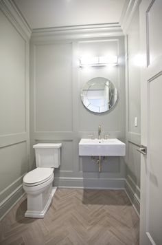 gray paneled powder room walls, floating sink & herringbone floors