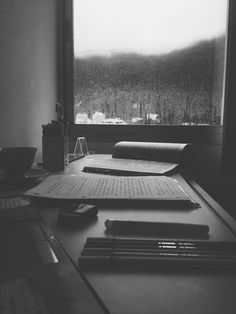 Perfect day for learning at home. Rain, book, papers, desk, window...