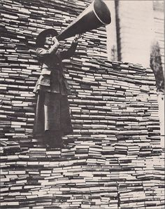 A barker stands on a large book pile, calling for book donations for the New York Public Library on Fifth Avenue, early 1900's
