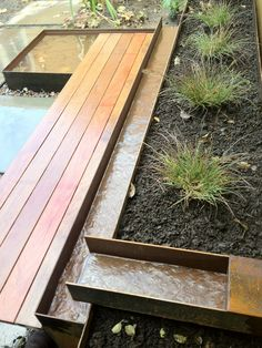 Wood, Steel, Stone | Wood bench, steel water feature, concrete pavers.