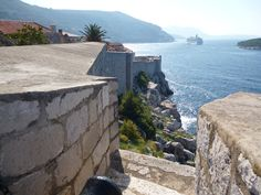 Looking out over a cannon to see the sea and a cruise ship, Dubrovnik wall.