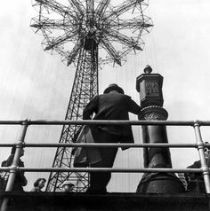 Man standing near Parachute Drop, Coney Island, 1949  Harold Feinstein