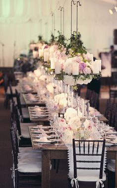 Iron floral chandeliers suspended above the head table oval table.  If possible, it would be great to do this set.