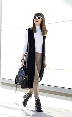 Jenny Bernheim is wearing an ultra sleek black sleeveless jacket over a simple white polo neck top and paired with heeled combat boots which we adore! This look just screams 'fierce', and we recommend you try it! Brands not specified.