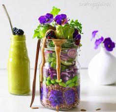 Salade bicolore aux fleurs en bocal Vert et violet, un joli duo qui en met plein les yeux et qui réveille les papilles. A table !  La sauce : vinaigrette à base de vinaigre balsamique  Le bon mix : quinoa + fèves + chou rouge + concombre + oignon rouge + avocat + tomate verte + mûres + pensées  Le drink : smoothie avocat