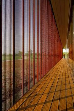 Red mesh shades the interior of a farm visitor centre by Vector Architects