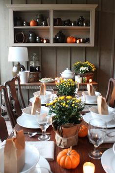 Chili Party Decor for Fall: Simple table setting of votives and mini pumpkins.  Wrap a grocery store plant in craft paper and secure with twine.