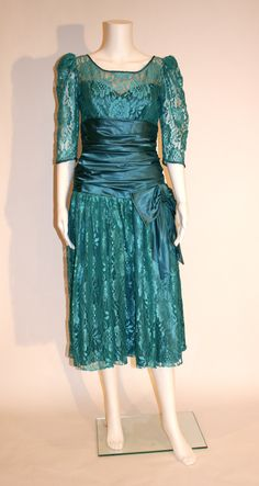 Gleaming deep teal lace over satin 80s prom dress with puffed sleeves, side ruching, drop waist, and asymmetrical sash with oversize side bow. The skirt portion is lined with tulle for flare and fulln