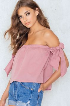 $29 It can't be any hotter than this! The Off Shoulder Tied Sleeve Top by NA-KD comes in dusty pink and features an elastic band to prevent the blouse from gliding down and decorative ribbons on the shoulders. Wear it with a pair of high waister vintage shorts!