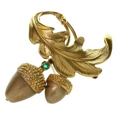 Raymond Yard Emerald Oak Acorn Leaf Yellow Gold Brooch features a pair of acorns and an oak leaf crafted in delicate textures of 18k yellow gold and accented with a prong-set faceted natural green emerald of an estimated 0.20 carats. A rare circa 1950s design.