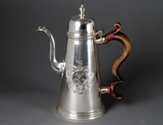 "RARE & IMPORTANT PAUL DeLAMERIE STERLING SILVER COFFEE POT English. London. 1714. Of lighthouse form engraved with a crest and applied with a double scroll wood handle. Height 9 5/8"". (28 oz) Note: As Lamerie entered his first maker's mark at Goldsmiths' Hall on February 5, 1713, this coffee pot is one of the earliest surviving works by him. There is only one other coffee pot by Lamerie marked in 1714 known (illustrated in Susan Hare, Paul de Lamerie, 1990, Cat. No. 5, Illus. p. 33)"