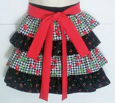 Retro Half Apron, Black Gingham, Cherry, Cherries, Red and Black, Ruffled Apron, Cherry, Ruffles, KitschNStyle What says RETRO better than gingham and cherries? This retro half apron has ruffled layers of black and white gingham covered in cherries alternating with smaller cherries on black. The solid red waist ties are each 42 long and can wrap around to tie in front. The solid black waistband is 21. Length is 16 from top of waistband. KitschNStyle is all about quality - beautiful and du...