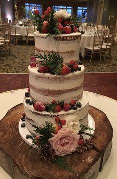 Naked wedding cake garnished with flowers and fresh fruit.