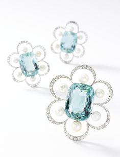 Aquamarine, natural pearl and diamond brooches, Georges Fouquet, 1908. Designed as five graduated floral motifs, each set with a cushion shaped aquamarine within a petalled border of circular-cut and rose diamonds and natural pearl accents, on a later tiara frame, five detachable brooch pins.