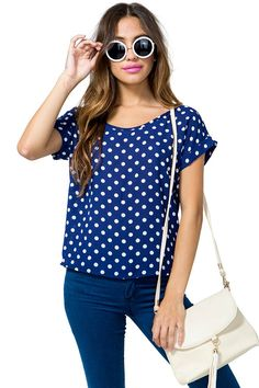 A cute spot on tee featuring an allover polka dot print and a round neck. Rolled short sleeves. Peekaboo back with a button loop closure. Finished hem. Boxy fit.