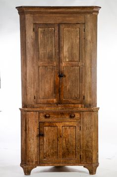 """PENNSYLVANIA DECORATED CORNER CUPBOARD.  Mid 19th century, pine. Two piece low waisted corner cupboard. Stacked crown molding with a beaded case. Paneled doors with a cock beaded drawer. An applied bracket base. Grained surface has alligatored which was painted over the original red paint. 93""""h. 46.5""""w. 25""""d. The cupboard takes a 32.5"""" corner.  Estimate $ 1,200-1,800"""