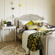 Decorate your bedroom with complementary colours. Here the citrus shades in the flowers, cushions and wall hangings, work well with the cool grey tones in the bedlinen.
