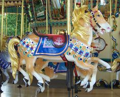 National Carousel Association - The Worlds of Fun Carousel - Illions Jumper..Brilliant gold tossed mane and tail with colorful trappings a characteristic of M.C. Illions.