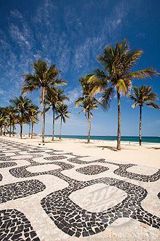 Palm trees by the distinctive wavy tile pavement at Ipanema Beach, Rio de Janeiro, Brasil.