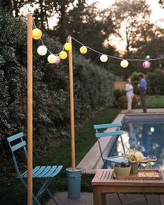 No need to bring the party indoors after the sun goes down, even if your yard isn't lit. String up lights to illuminate the festivities. Don't have a place to hang them? Wooden poles anchored in flower buckets filled with garden gravel can be set up anywhere there's level ground, and they help define an outdoor gathering place. Arrange poles in a square, circle or row, and string the lights from one to another.You'll find 6- to 8-foot wooden poles, screw eyes, plastic fastener...