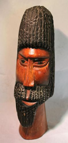 This serious guy is a hand carved and hand painted African tribal statue of a mans head. He has fabulously detailed hair and beard, which are painted black. He has been varnished so that he has an attractive sheen.  Size: 10.75x4x3