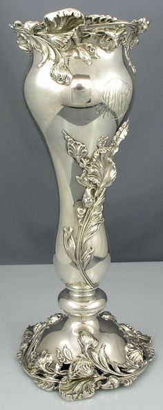 A sterling silver art nouveau flower vase with applied three dimensional art nouveau flowers on the pedestal.