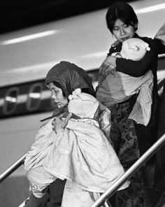 Vietnamese refugee women carry children off the plane at Montreal's Dorval airport Nov 26, 1978.   THE CANADIAN PRESS/John Goddard