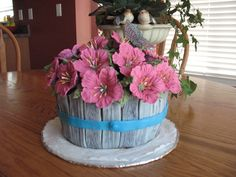 The petunias are royal icing, the basket's wooden slats are fondant that I stamped with a woodgrain stamp. The butterfly is rice paper.