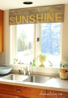 Instead of a traditional kitchen window treatment, use reclaimed wood and stencils to create a one-of-a-kind window treatment.
