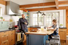 Homeowner Ian Blaine and son Anders gather around a new kitchen island, which is tucked into the kitchen's work zone. The space's salvaged-fir box-beam ceiling echoes the Tudor-style home's exterior details.