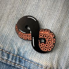 Enamel pin of a tentacle shaped like an infinity sign. It is black, white, and salmon colored. Shown on a denim jacket.