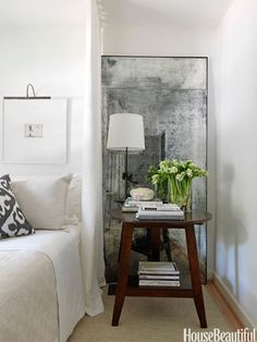 A mirror is placed next to the bed to hide an awkwardly placed window. Design: Lindsey Bond.