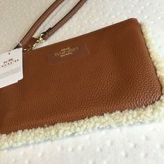 """hp.  coach wristlet New with tags. Comes with tag on, authentication cards, new. Size 6 3/4"""" x 4"""". Wrist strap. Great saddle brown color with fur accent. Beautiful! ❌No trades or PayPal.  Quick shipping Offers welcome through """"Make an Offer"""" feature. Coach Bags Clutches & Wristlets"""