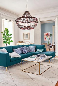 A modern, fresh living area - the modern, bright looking sectional in dark turquoise really pulls the otherwise very neutral room together beautifully.