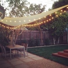 Backyard with pavers and shade sail with string lights | Yelp