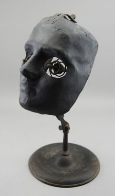 """Device used by ophthalmology students to hone surgical skills. Two spring mounted brass eyeholders with pincers would hold pig eyes for future ophthalmologists to practice their craft before operating on human patients"