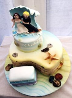 Two tier beach theme wedding cake with caricatures of the bride and groom as the wedding cake topper surfing on a wave. The wedding cake has the beach and surf airbrushed on the actual cake, and decorated with seashells, pebbles and a van. From www.novelty-cakes.net ........ #wedding #cake #birthday