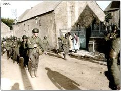 U.S. Army troops of the 2nd Infantry Division march through the liberated village of Colleville-sur-Mer on D-Day+2, 8th of June 1944. The beach next to the coastal village was one of the principal beachheads during the D-Day landings on 6 June 1944, designated Omaha Beach. Colleville-sur-Mer, Calvados, Lower Normandy, France.
