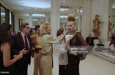 Yves Saint Laurent Prepares His Fall-winter 1999-2000 Couture Collection. En juillet 1999, Yves SAINT LAURENT supervise les préparatifs du défilé de la collection haute couture YSL, Automne Hiver, 1999-2000, entouré de collaborateurs qui finalise son allure, observant le top model Esther CANADAS vêtue et coiffée pour la présentation. Au fond assis dans un angle de la pièce, Pierre BERGER le PDG d'YSL Couture observe la scène.