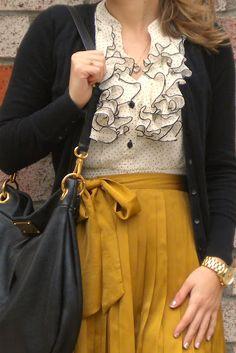mustard skirt, ruffle shirt, cardigan, black bag.