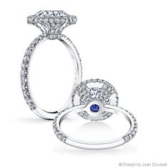 LOUISE is a handcrafted Jean Dousset Diamonds engagement ring design featuring a seamless diamond halo - JeanDousset.com - pictured with a Round Brilliant cut diamond, set in Platinum, and a blue sapphire for The Signature Stone®. #RoundCut #EngagementRing