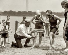 """""""June 30, 1922. Washington policeman Bill Norton measuring the distance between knee and suit at the Tidal Basin bathing beach after Col. Sherrill, Superintendent of Public Buildings and Grounds, issued an order that suits not be over six inches above the knee."""""""