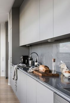 a minimalist grey kitchen with a concrete backsplash covered with a glass screen completely for keeping it clean