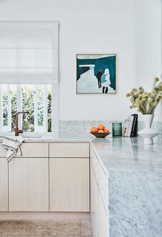 Marble benchtops add a touch of luxury in this coastal kitchen which features blonde timber veneer kitchen cabinetry and limestone flooring.