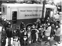 Children in the snow, 1940's era, waiting in line a the Mount Vernon Public Library Bookmobile, vintage photograph