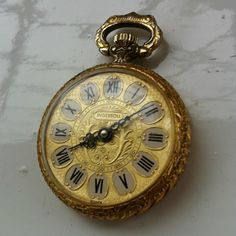 This is a very pretty gold colored ladies pocket watch made by the Swiss Ingersoll company. This vintage piece has a richly ornate gold dial signed 'Ingersoll'. The back has lovely embossed flower detail. Humankind has always recognized the passing of time and has tried to measure and record that passing.  Recorded or not - Time is passing!